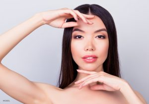 Asian American Model Touching Forehead and Chin With Hands