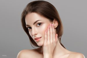 Model With One Hand Firmly Placed on Cheek